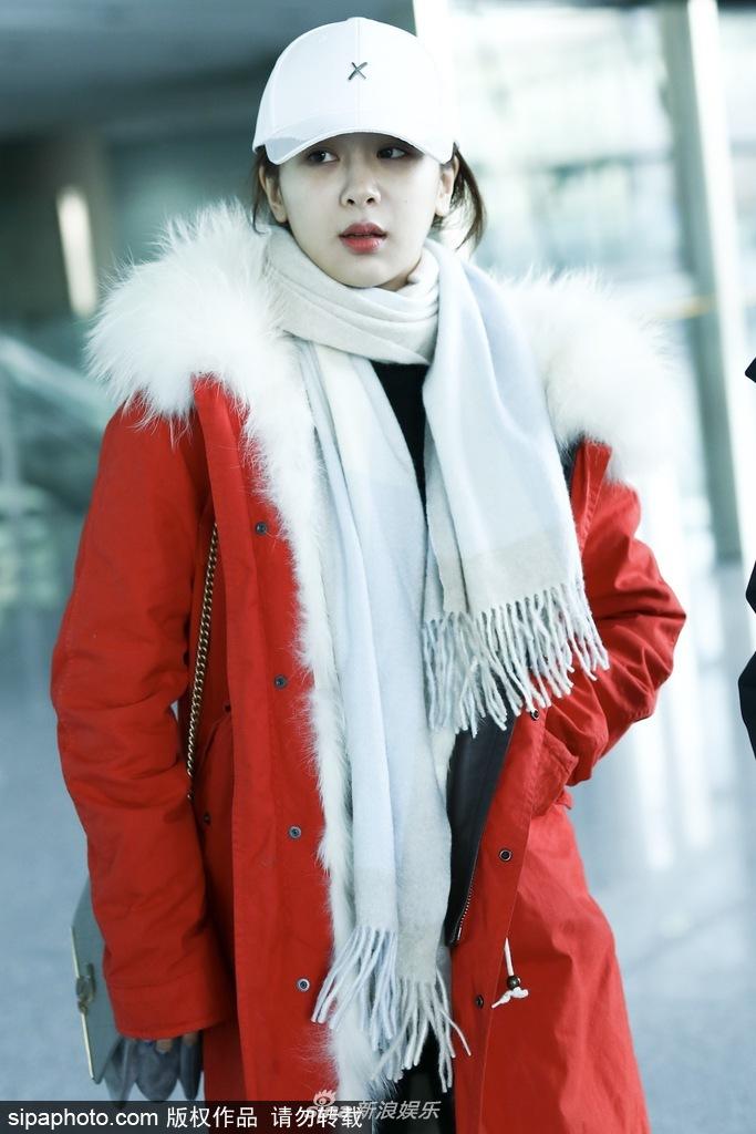 身机场。她身穿红色外套显喜庆
