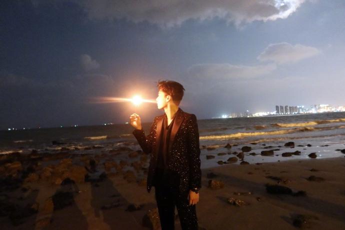 李易峰拿着一根烟花棒 在海边拍了一部大片 穿亮片西装