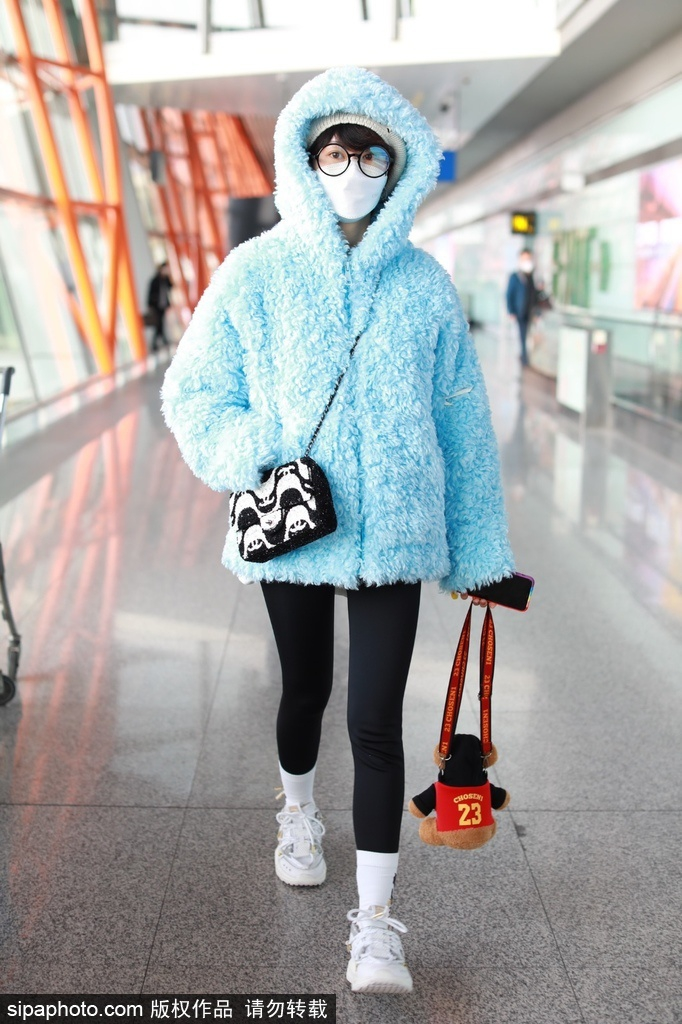 旭佳宇穿着蓝色棉毛外套 穿着黑色打底裤 出现在机场的眼神又傻又可爱