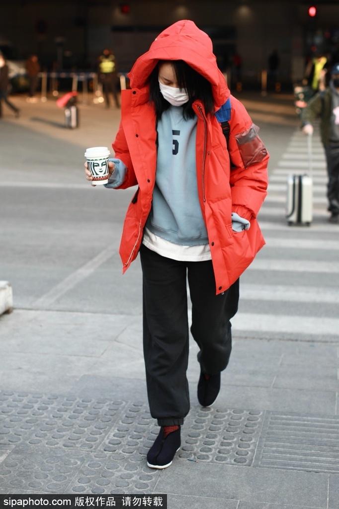 罗英穿着红色棉衣 踩着棉花出现在机场 穿着休闲的版型 满是低调