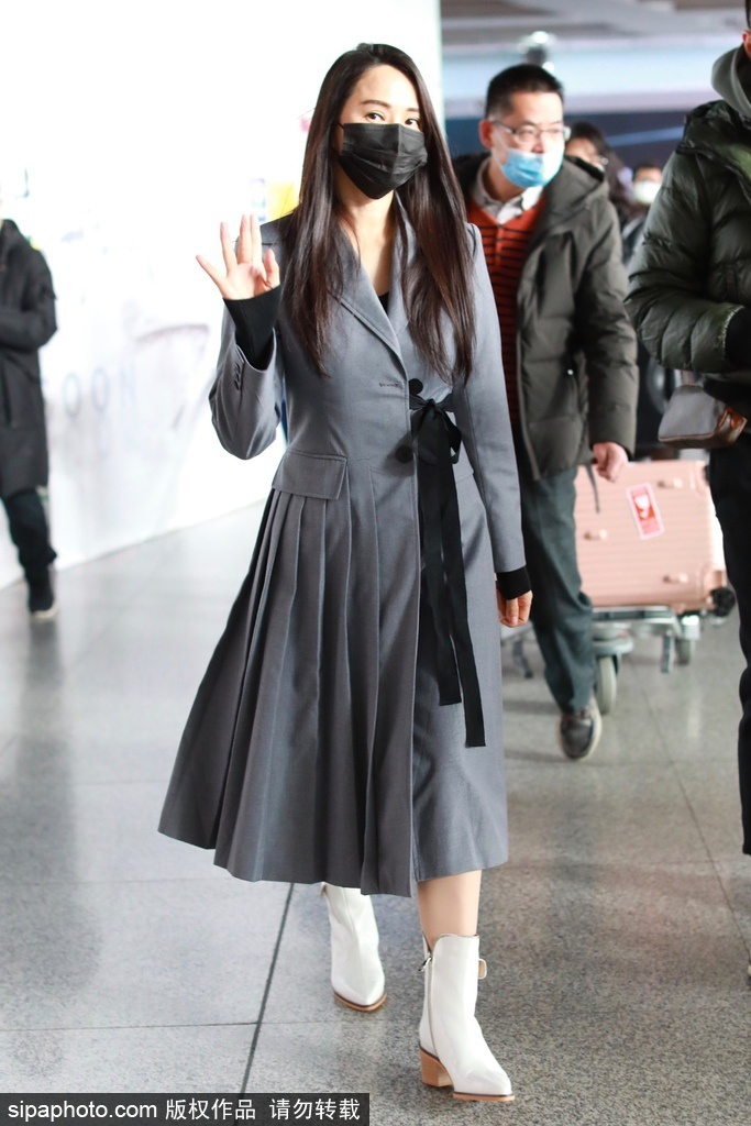 伊能静机场脱掉羽绒服 穿灰色裙子拖鞋做高跟短靴