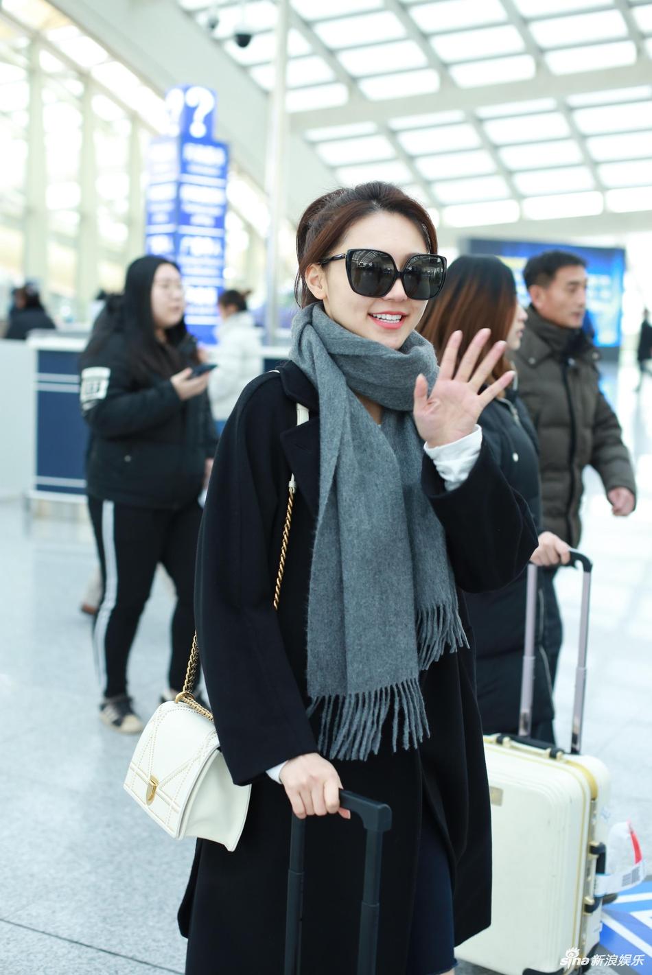 组图:黄梦莹裹灰色围巾亮相机场 梳马尾辫对镜头招手心情好