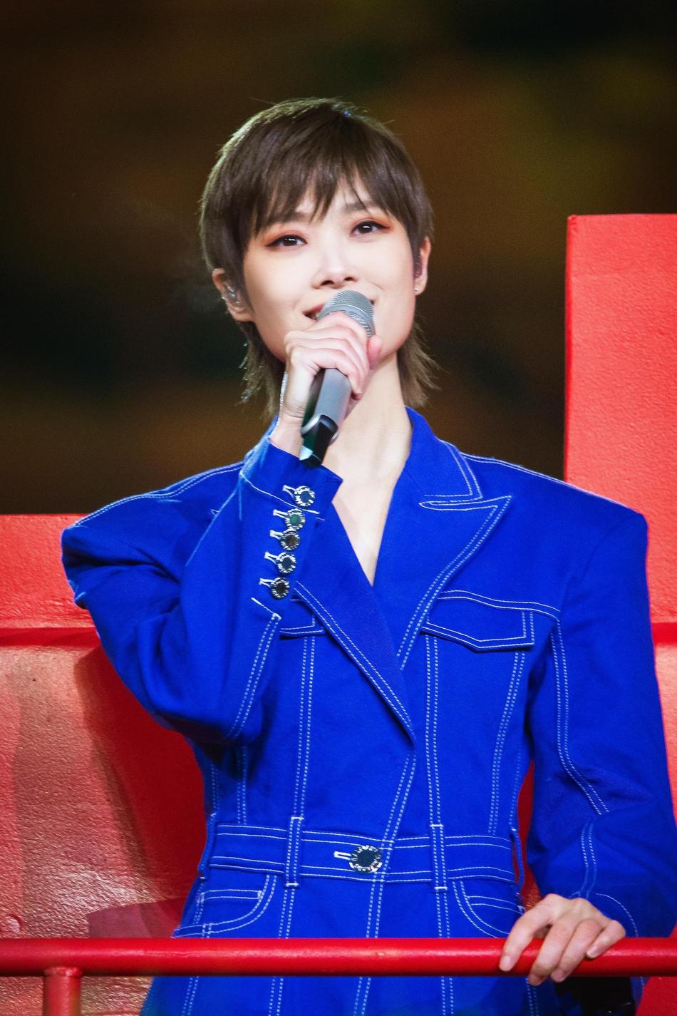 组图:李宇春深蓝色套装现身郑州分会场 站拖拉机上唱脱贫主题曲