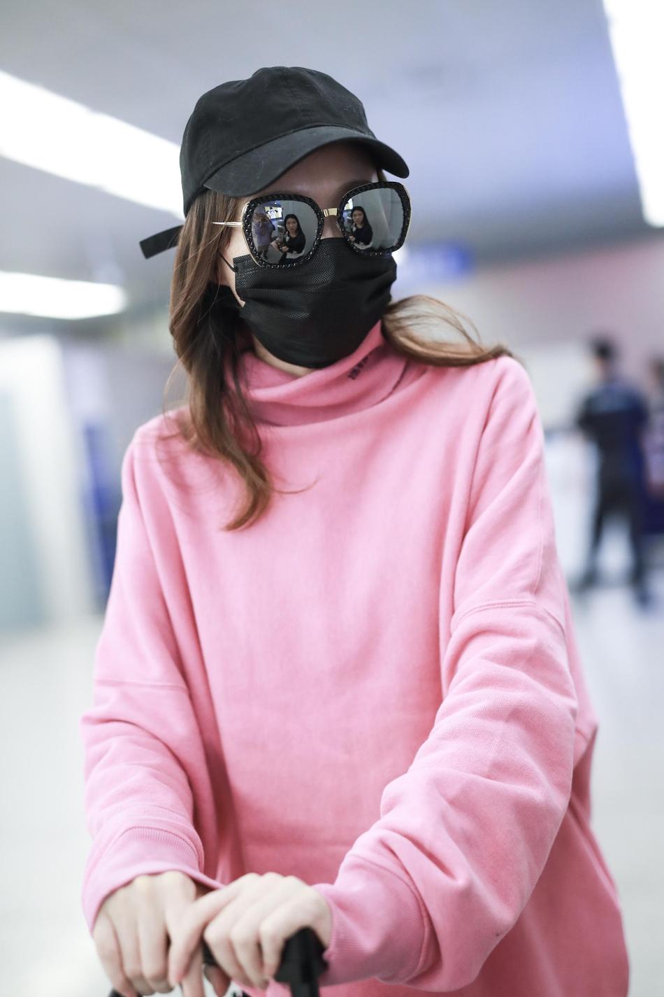 现身机场。她戴着帽子口罩十分