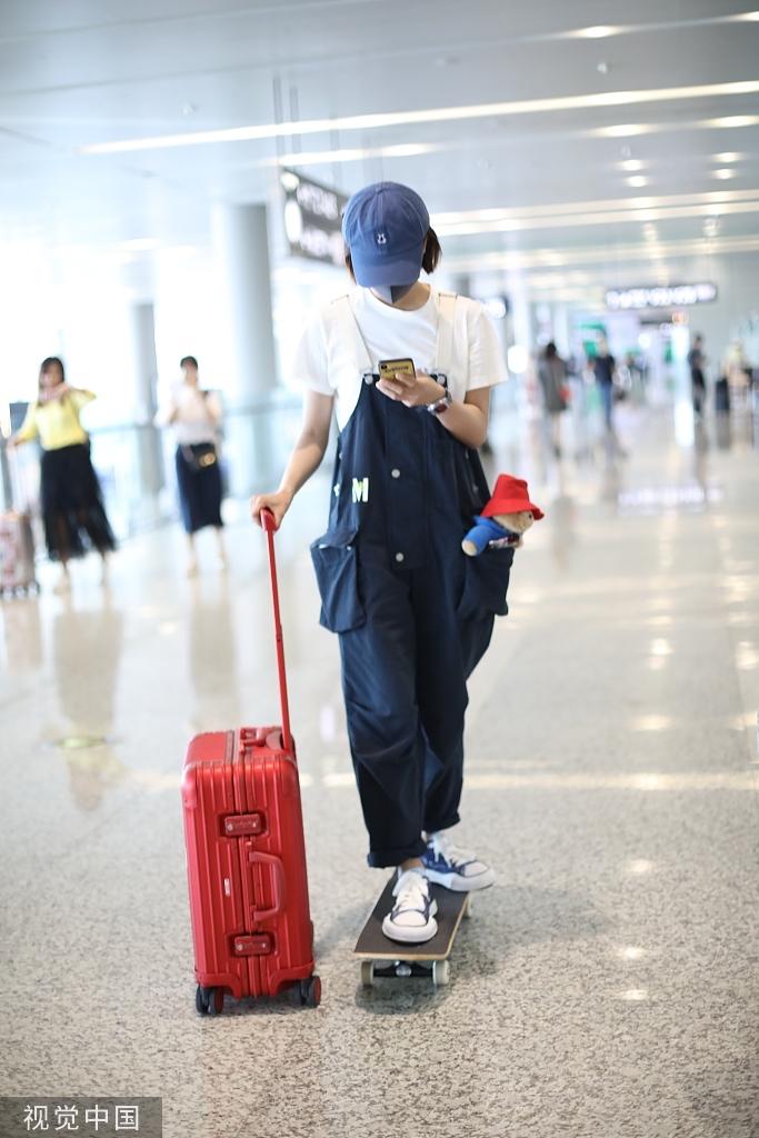 组图:王珞丹口袋装娃娃暴露少女心 机场单手拉箱玩滑板引新潮流
