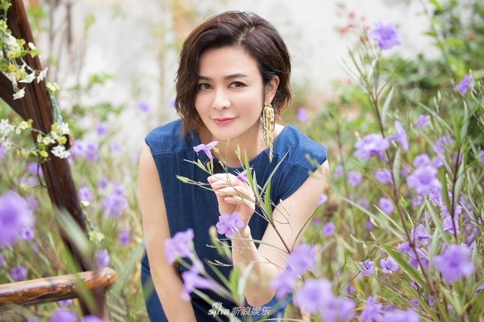 组图:关之琳穿蓝色长裙置身花田 人比花美展示迷人微笑