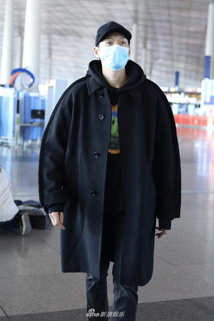 魏大勋黑色外套中的卡通T保持温暖和精力充沛 戴着帽子