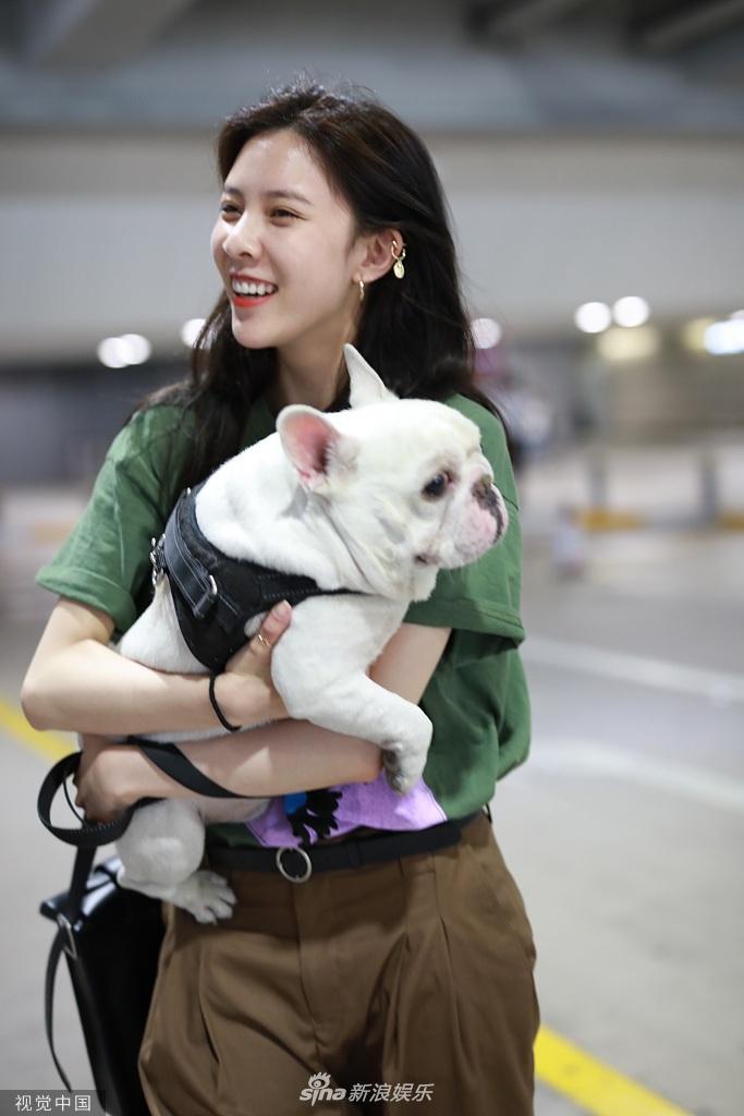 组图:宋妍霏抱爱犬现身机场 心情大好笑的见牙不见眼