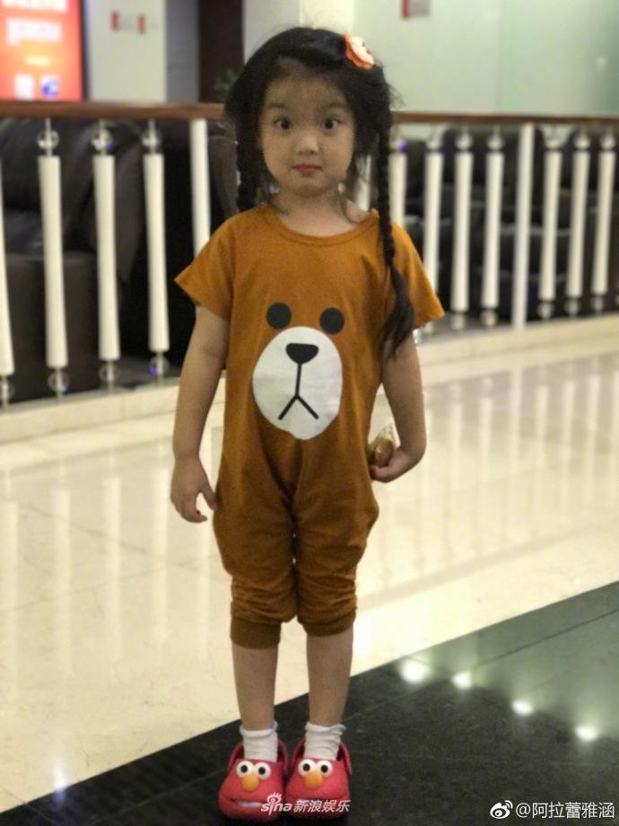 """并且配文""""行走的表情包"""",照片中她身穿棕色睡衣,扎着两个小"""