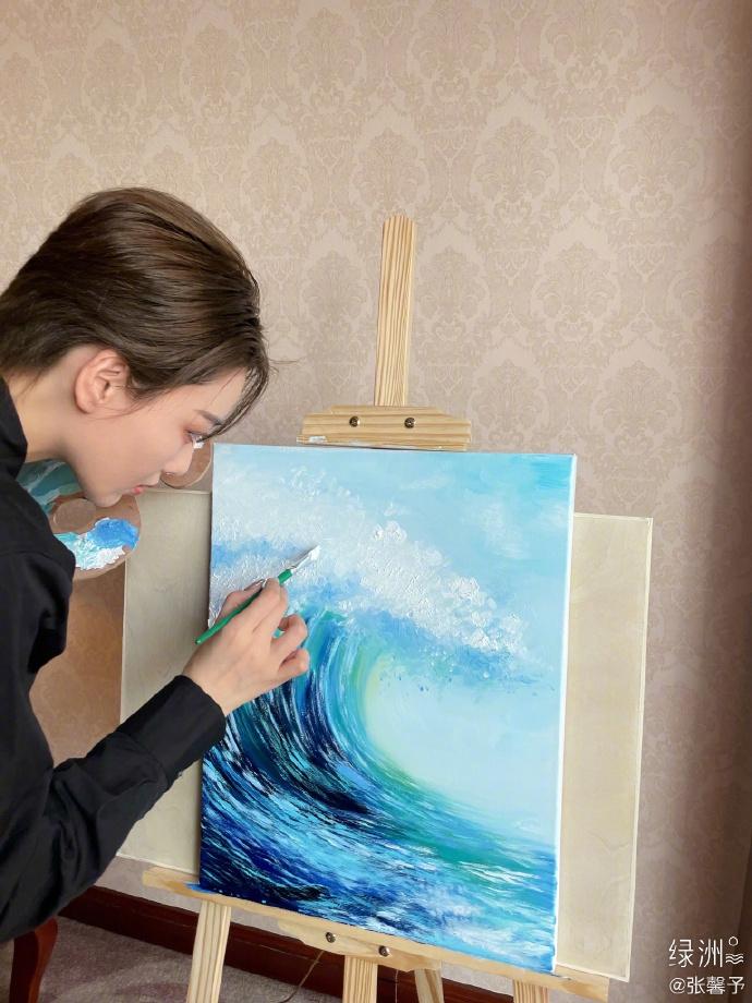 请为张信伟《浪姐2》画一个小浪花 全黑装手里拿着画笔很有魅力