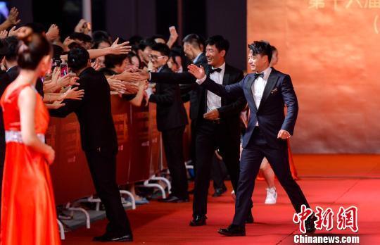 获奖嘉宾段奕宏、郭晓东在走红毯时与观众互动。 胡耀杰 摄