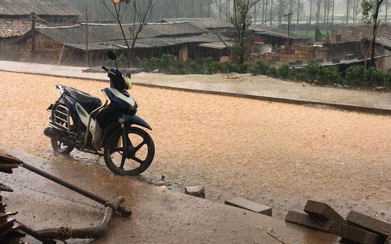 """一下雨,村裏的路面就變成""""土黃色"""" 新京報記者 張羽 攝"""
