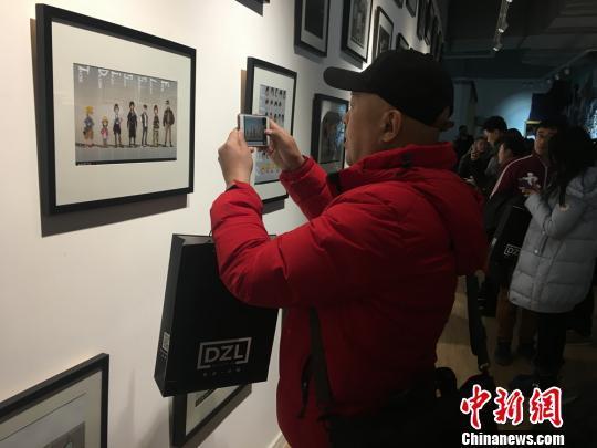 图为观展者纷纷举起手机拍照留念。 李英 摄