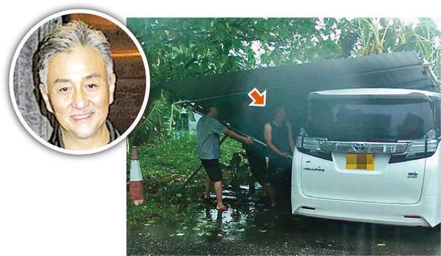 吴岱融(中)与邻居在强风下合力处理吹倒的棚架免伤及他人。