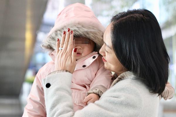 组图:朱丹素颜抱娃现身机场 为女儿挡风遮脸