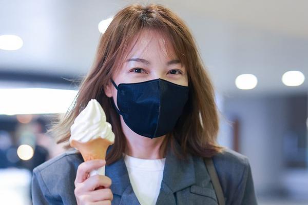 吴昕手拿冰淇淋现身机场 绑带西装时尚帅气