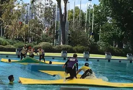 志愿者水池中托举浮板