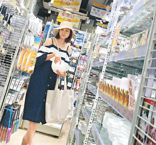 谢安琪在家居店选购日用品,拿起来慢慢看。