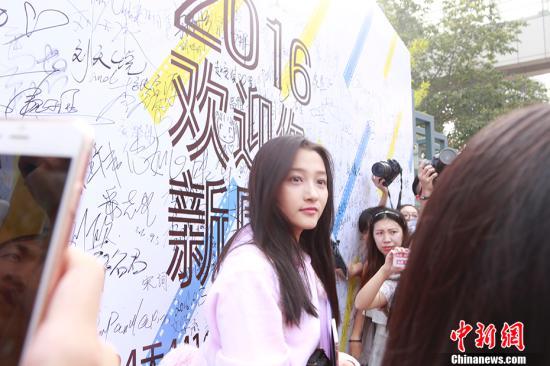 """9月4日,""""国民闺女""""关晓彤身穿一袭粉色帽衫,现身北京电影学院报到,遭媒体围堵。 中新网记者 翟璐 摄"""