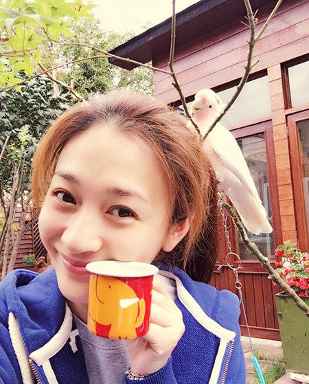 9月18日,李小冉再次晒出素颜照,照片中的她手中拿着红色小杯子,和身后