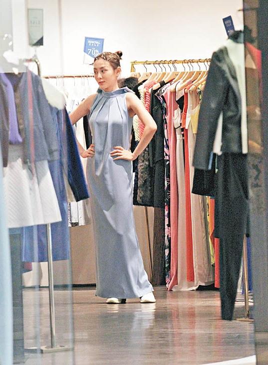 何佩瑜走到名店试晚装,还在镜前照来照去。