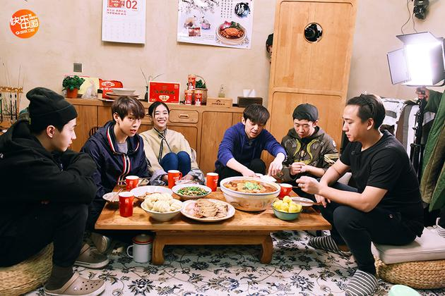 一大家子人围坐在小桌前享受晚餐