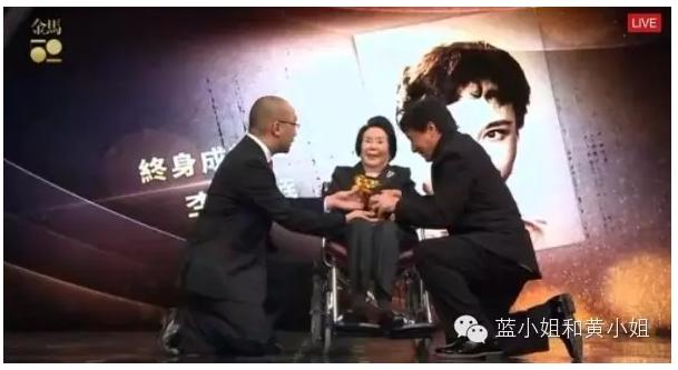 成龍(右)下跪為李麗華頒獎。