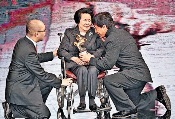 在前年金马奖,成龙(右)以单膝下跪颁奖给李丽华(中)。