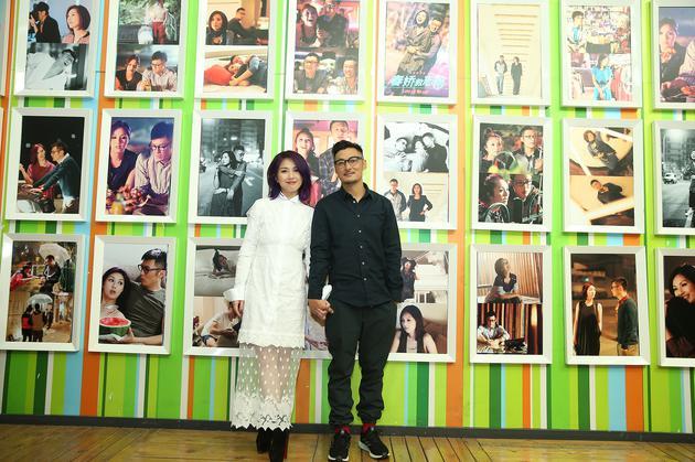 阿乐和千嬅在志明春娇照片墙前合影