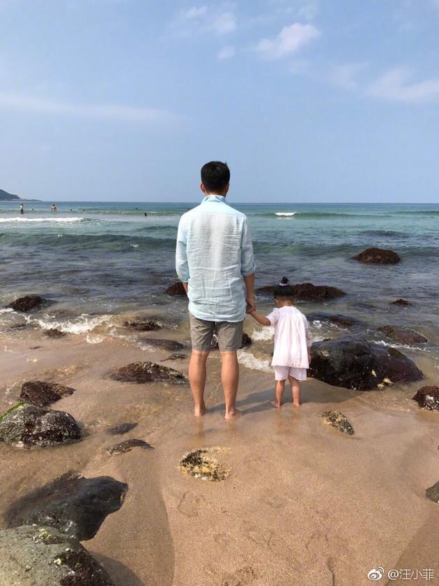 汪小菲与女儿手拉手在礁石边