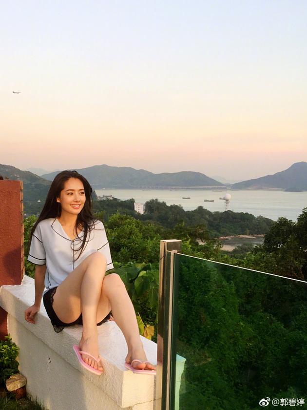 郭碧婷坐阳台围栏上拍照笑容惬意 网友:太危险了