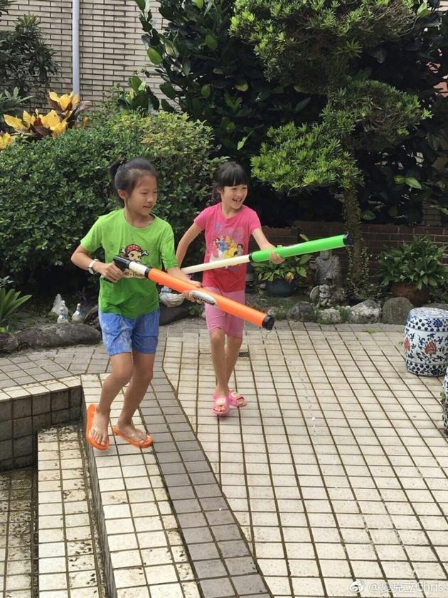 夏天与伙伴玩水枪笑容灿烂 老爸直呼:打败热天气