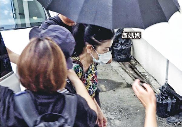 亲友撑起雨伞护送卢凯彤妈妈进入殓房