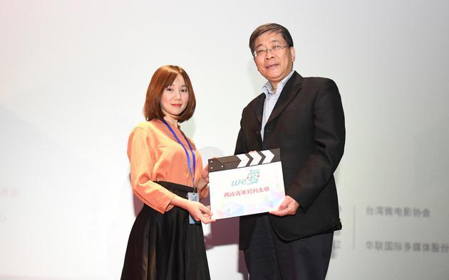 上海市人民政府台湾事务办公室主任李文辉给交流营营员代表赠送场记板