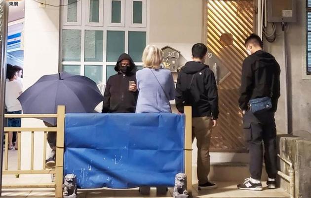 吴耀汉用雨伞遮挡