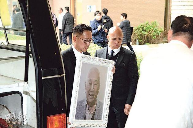 许晋亨捧着父亲许世勋的遗照
