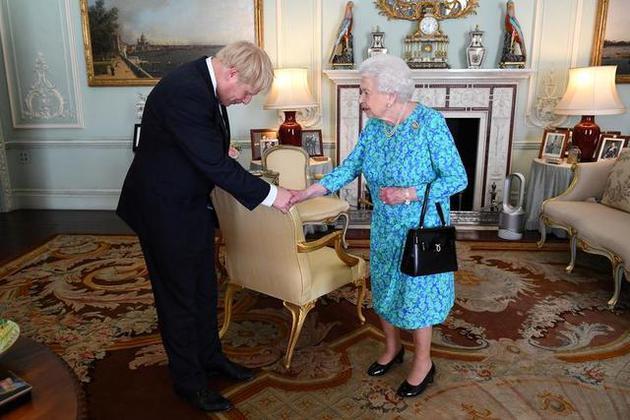 资料图:约翰逊与英国女王握手合影(路透社)