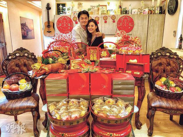 萧润邦搂着江若琳在放满客厅的大礼前合照留念。