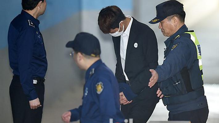 郑俊英现身法院出席公审准备 戴手铐低头不语