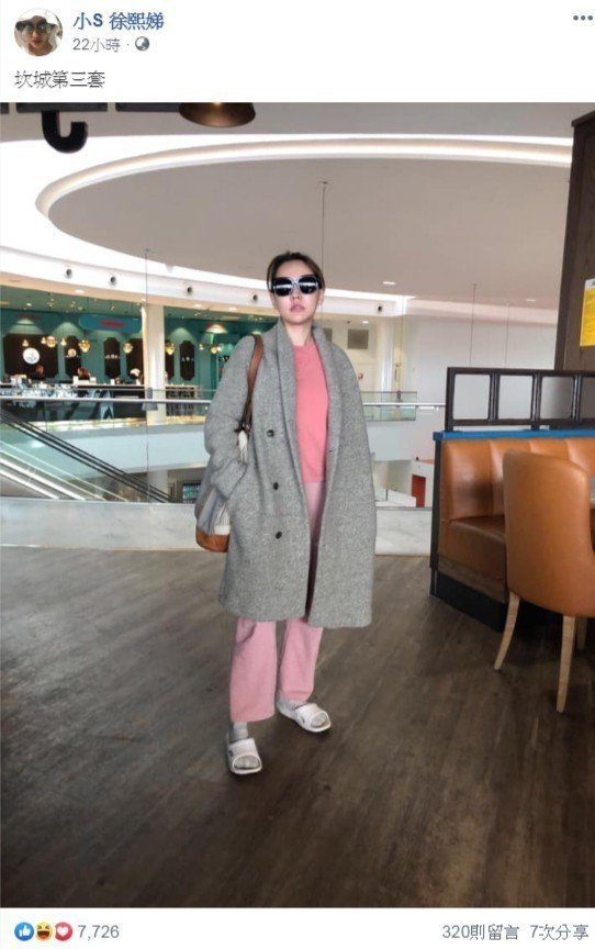 她穿著粉紅色系的衛衣,外面搭著灰色外套與拖鞋、襪子。