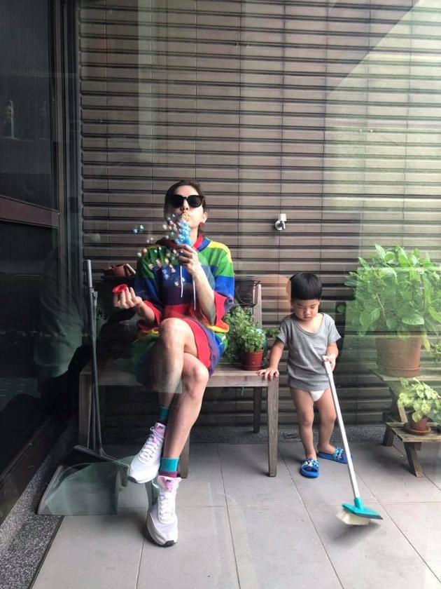 她兒子勁寶只穿著上衣和尿布入鏡,乖巧地在一旁掃地。