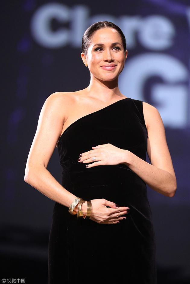 梅根王妃出其意外的身穿了一件时兴的单肩暗色裙子,并且还给指甲涂上了颜色。