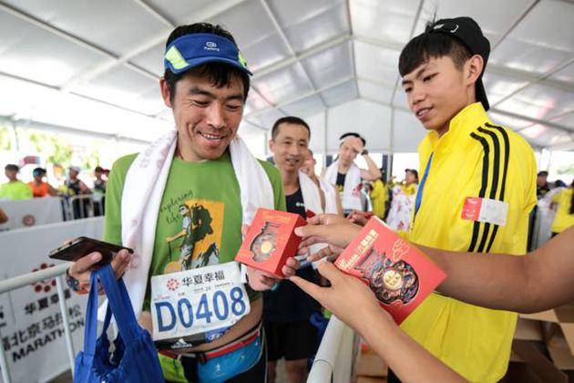 完赛选手跑到终点处领取六福珠宝足金奖牌开心不已
