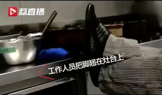 工作人员把脚翘在灶台上