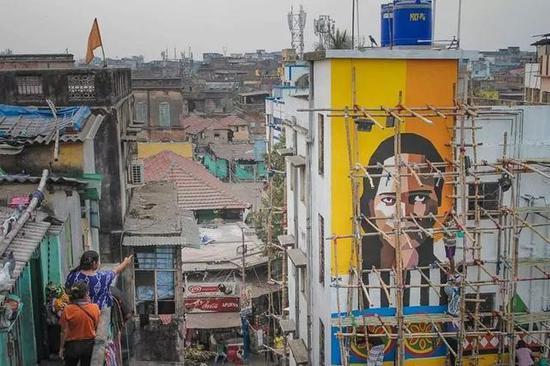 印度红灯区外,一些艺术家正在创作壁画。