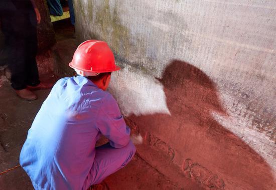 相關工作人員正在對藏經洞經文進行專業除塵保護