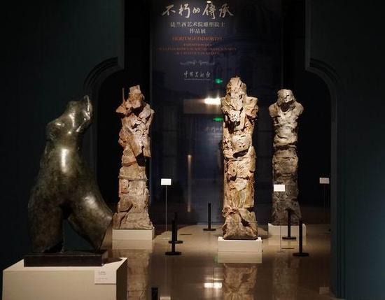 展览现场,后为布里吉特·泰尔齐耶夫《守夜人》系列雕塑