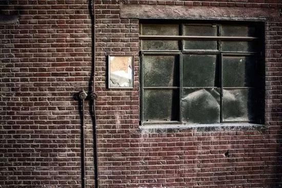 泛黄的墙体和脏乱的窗