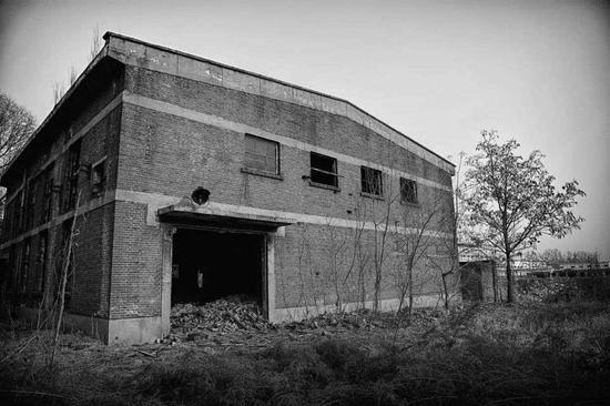 △厂房外瓦砾散落荒草之间