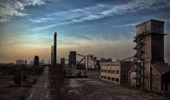 厂外一片狼藉,黯淡的建筑与天色对比
